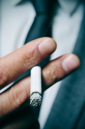 hombre fumando: un hombre que llevaba un traje de fumar un cigarrillo