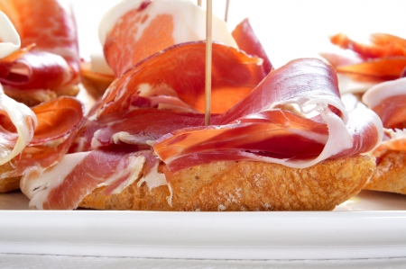 toothpick: closeup of a plate with some typical spanish pinchos de jamon, serrano ham served on bread