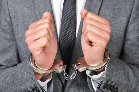 a man wearing a suit, with handcuffs in his wrists photo