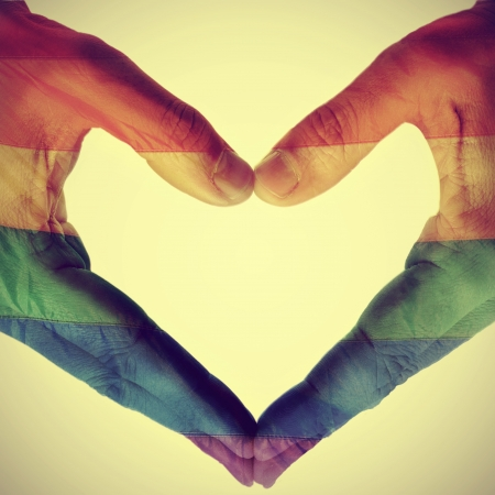 picture of man hands forming a hear patterned with the gay pride flag, with a retro effect photo
