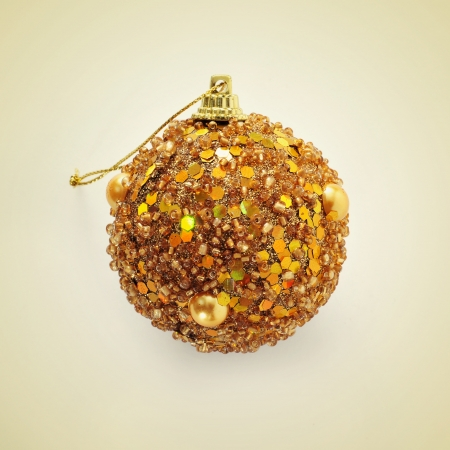 picture of a golden christmas ball on a beige background, with a retro effect photo