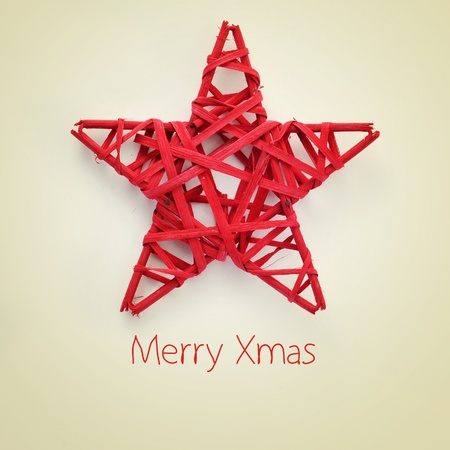 a red christmas star and the sentence merry xmas on a beige background, with a retro effect photo