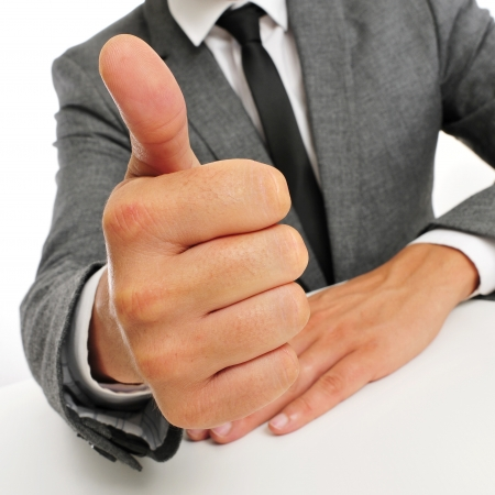 man wearing a suit sitting in a table giving a thumbs up signal Stock Photo - 21993705