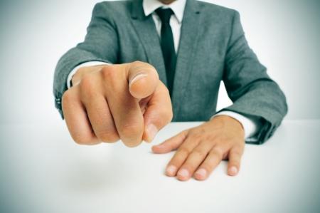 man draagt een pak zitten in een tabel met de vinger wijzen naar de waarnemer