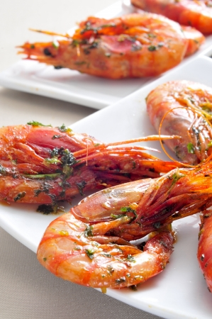 closeup of a plate with spanish shrimps cooked with garlic and parsley, on a set table photo