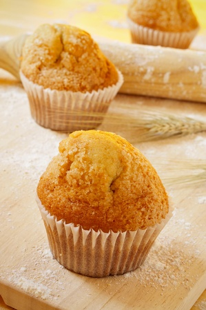 madeleine: closeup of some magdalenas, typical spanish plain muffins, on a wooden surface peppered with flour and a rolling pin and some wheat ears Stock Photo