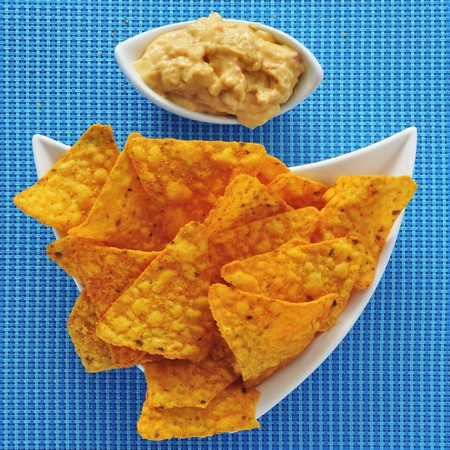 a plate with tortilla chips and a bowl with hummus, on a blue fabric background photo