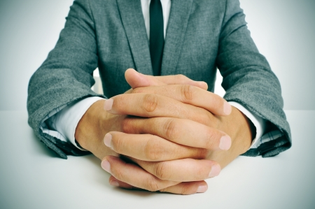 man wearing a suit sitting in a table with clasped hands photo