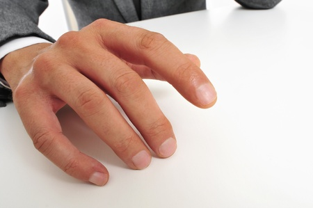 impatience: man wearing a suit sitting drumming his fingers on the desk Stock Photo