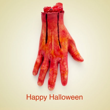 picture of a scary amputated hand and the sentence happy halloween on a beige background, with a retro effect photo