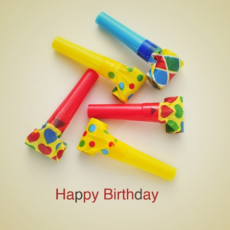 picture of some party horns of different colors and the sentence happy birthday on a beige background, with a retro effect Stock Photo