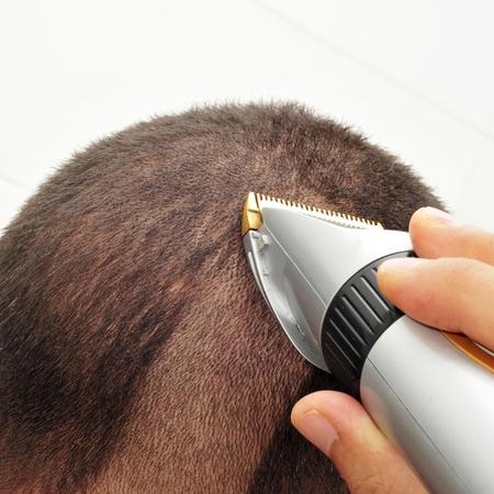 hair dressing: a man man cutting his hair with an electric hair clipper Stock Photo