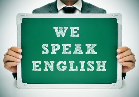 a man wearing a suit holding a chalkboard with the sentence we speak english written in it photo