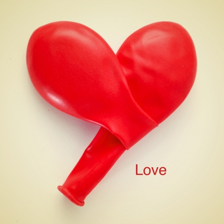 picture of two red balloons forming a heart and the word love written on a beige background, with a retro effect photo