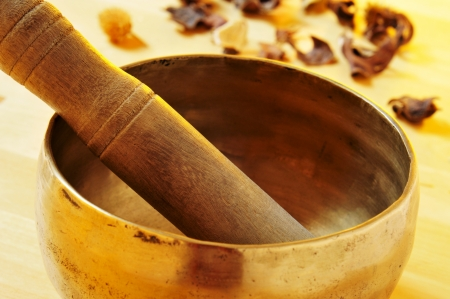 closeup of a tibetan singing bowl with its mallet on a table with dried flowers photo