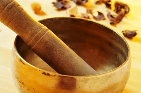 singing bowl: primo piano di una ciotola di canto tibetano con il suo maglio su un tavolo con i fiori secchi