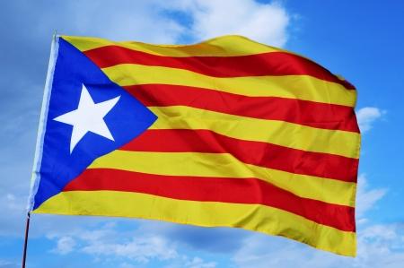 separatist: an estelada, the Catalan separatist flag, waving over the blue sky