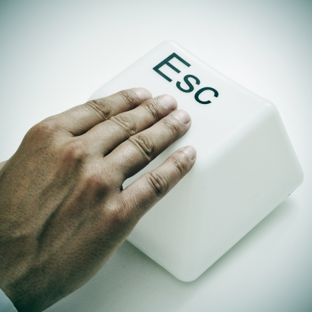 escape key: a man pressing a giant escape key with his hand Stock Photo