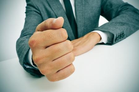 director de escuela: hombre que llevaba un traje dando un puñetazo sobre la mesa Foto de archivo