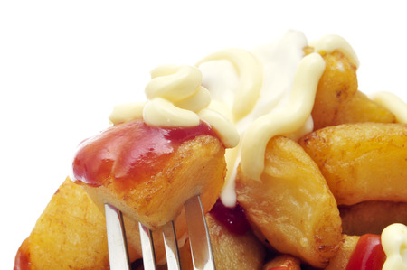 closeup of some typical spanish patatas bravas, fried potatoes with a hot sauce, on a white background photo