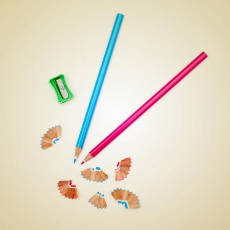 sacapuntas: imagen de algunos lápices de colores y un sacapuntas sobre un fondo beige, con un efecto retro
