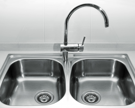sink drain: a double bowl stainless steel kitchen sink on a white granite worktop