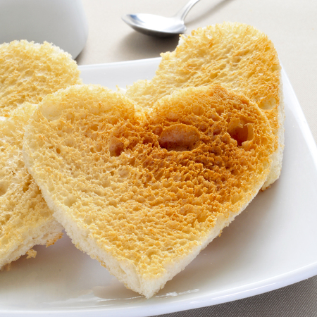 a plate with some heart-shaped toasts served on a set table photo