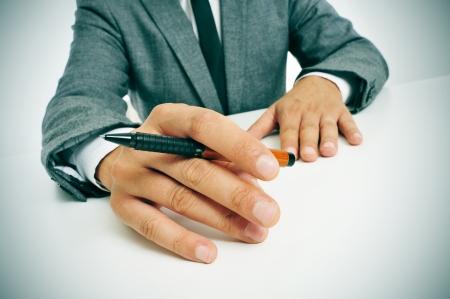 hombre escribiendo: hombre que llevaba un traje sentado en una mesa con un l�piz en la mano, ya la espera de la inspiraci�n Foto de archivo