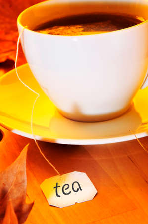 thirstiness: closeup of a cup with a tea bag being steeped, on a wooden table