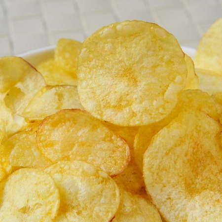 potato chips: closeup of a bowl with appetizing potato chips Stock Photo