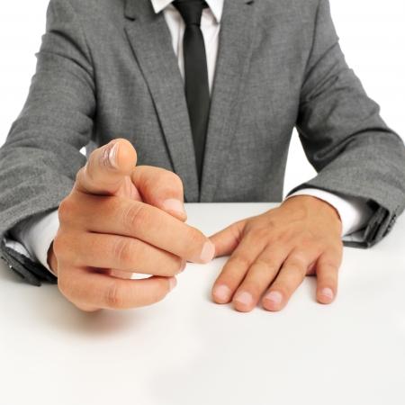dedo indice: hombre que llevaba un traje sentado en una mesa de señalar con el dedo al observador Foto de archivo