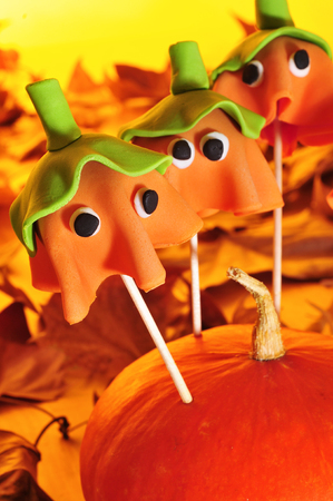 cake pops: some cake pops with the shape of ghost Halloween pumpkins, fixed in a pumpkin, with autumn dried leaves in the background