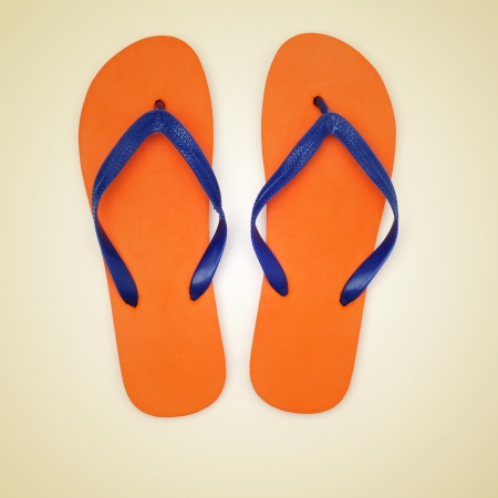 flip flops on the beach: picture of orange and blue flip-flops on a beige background, with a retro effect