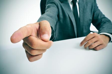 director de escuela: hombre que llevaba un traje sentado en una tabla que señala con el dedo la salida Foto de archivo