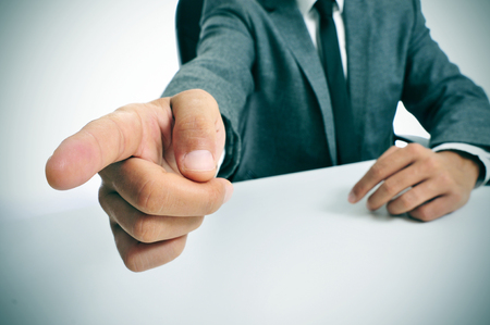 demotion: man wearing a suit sitting in a table pointing with the finger the way out