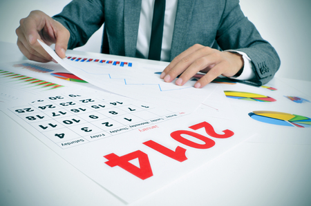 man wearing a suit sitting in a desk observing a pile of charts and with a 2014 calendar in the foreground photo