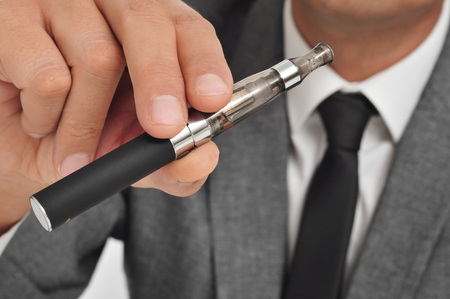 man wearing a suit vaping with an electronic cigarette photo