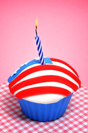 a cupcake decorated with the colors and stars of the flag of the United States, with a lit candle photo