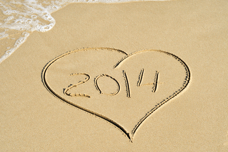 a heart drawn on the sand of a beach with the number 2014, as the new year, written inside photo