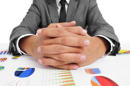 man wearing a suit sitting in a table full of charts with clasped hands photo