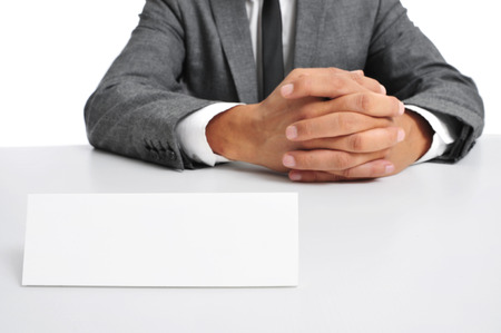 headman: a man wearing a suit sitting in a desk with a blank signboard in front of him with a copy-space