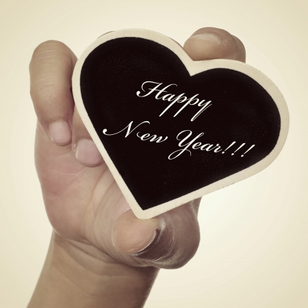 someone showing a small heart-shaped blackboard with the sentence happy new year written in it, with a retro effect photo