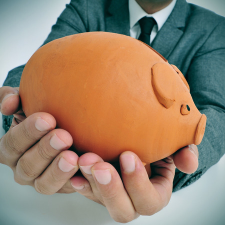 miserly: a man wearing a suit holding a piggy bank in his hands Stock Photo