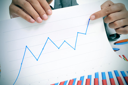 man wearing a suit sitting in a table showing a graph of economic growth photo