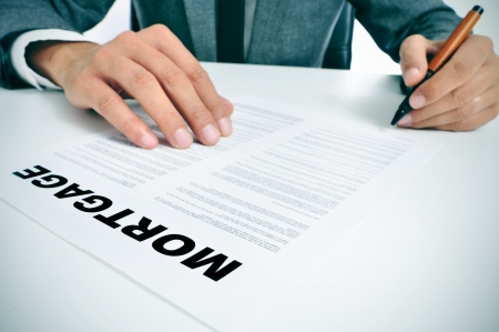 man wearing a suit sitting in a table signing mortgage loan contract photo