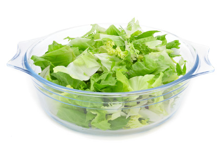 escarole: a glass bowl with mesclun, a mix of assorted salad leaves, on a white background