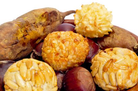 some panellets and roasted chestnuts and sweet potatoes, typical snack in All Saints Day in Catalonia, Spain, on a white background photo
