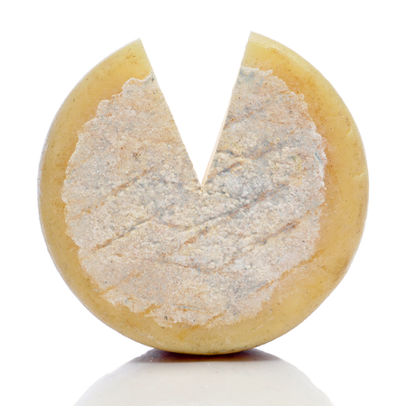 wedge: closeup of a cured cheese on a white background