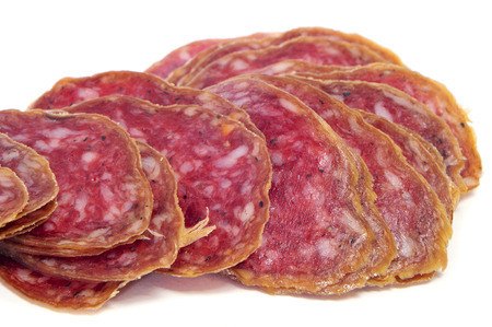 llonganissa: some slices of salchichon, spanish cured sausage, on a white background Stock Photo