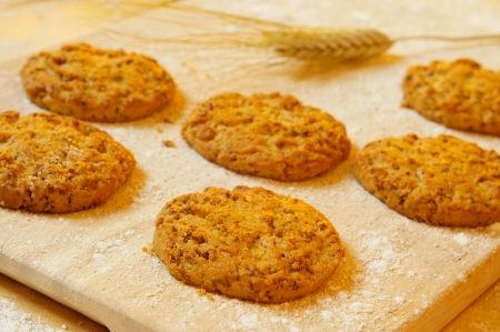 flak: some bran flake cookies on a wooden worktop stained with floor and with some wheat ears
